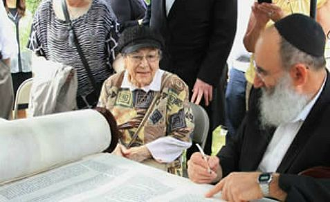 Holocaust survivor Marge Fettman sits next to Chabad scribe Rabbi Yochanan Nathan as he inscribed the closing verses of her Torah scroll with a quill pen and special kosher ink
