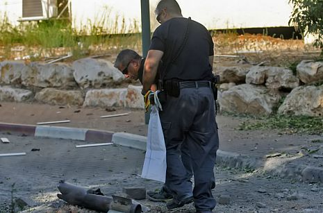 Security officials gather up remains of missile.  Shay Vaknin/Tazpit News Agency
