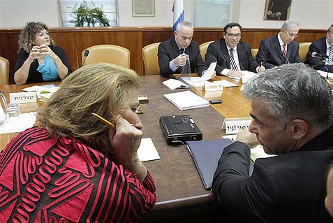 Justice Minister Tzipi Livni (L) speaking with Finance Minister Yair Lapid at a recent cabinet meeting. Livni opposes extending protection to pregnant women, Jewish and Arab, in Judea and Samaria from being fired.