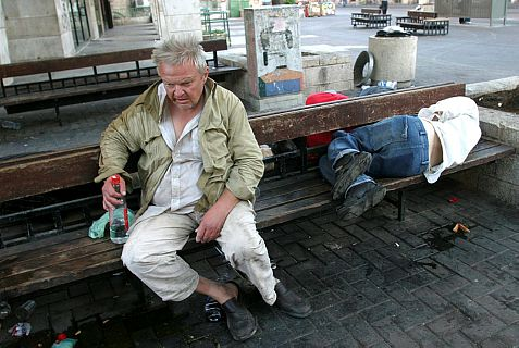 Homeless man wakes up with a hangover while his friend sleeps beside him on a bench near Jaffa Street in Jerusalem