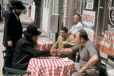 James Gandolfini as Tony Soprano (R), Steven Van Zandt as Silvio Dante (both seated at the table) and Tony Sirico as Paulie Gualtieri (seated by store window) forging a deal with Chasidic Jews on the third episode of the HBO series The Sopranos, aired January 24, 1999.