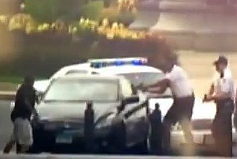 Police aim guns at woman driver, but she spun her car around and sped away before she crashed her car and police shot her dead.
