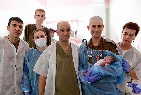 Israeli doctors hold baby Israel in the Philippines shortly after his birth.