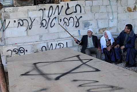 "Who did it? Arabs sit next to racist graffiti, signed ""Price tag"""