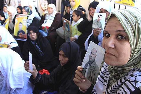 Gaza women holding up portraits of their jailed husbands and sons. By arresting terrorists, Israel has imposed hardship on their poor wives.
