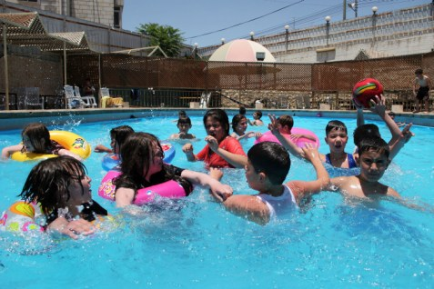 Arab Children swimming in a pool in Hebron, filled with water supplied by Mekorot, Israel.