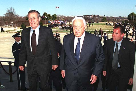 U.S. Secretary of Defense Donald H. Rumsfeld (left) escorts Israeli Prime Minister Ariel Sharon (center) into the Pentagon, March 19, 2001.