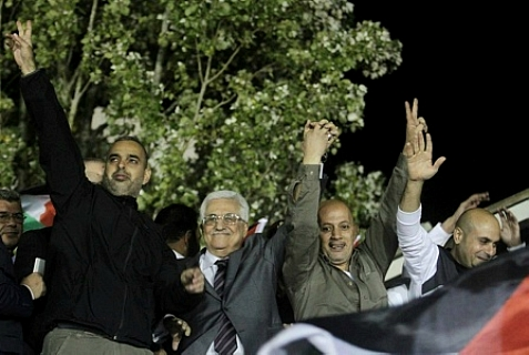 PA leader Mahmoud Abbas (center) holding hands in victory with Issa abd Rabbo (right of Abbas), murderer released from Israeli prison on Oct. 30, 2013
