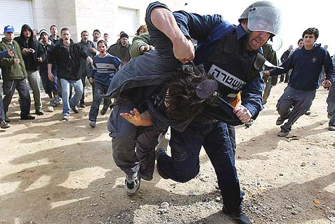 Israeli policeman forcibly removes a young Jewish settler from the town of Amona, in Mateh Binyamin Regional Council, Jan. 1, 2006. Rumor has it Netanyahu is preparing to repeat this painful experience in capitulation to American pressure.