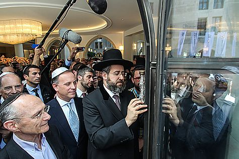 The Chief Rabbi placing the Mezuza on the entrance door of the Waldorf Astoria on opening day. Photo by Flash90