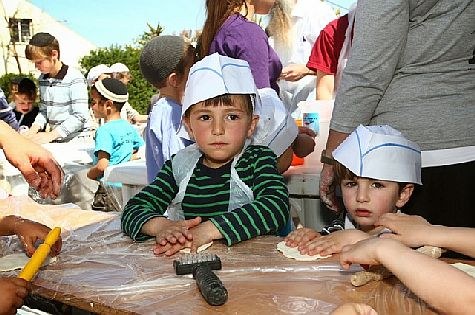 Two young matzoh bakers hard at work in the Binyamin community of Shiloh.