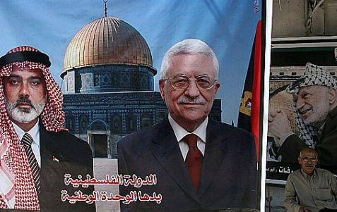 PA Chairman Mahmoud Abbas and Gaza-based Hamas leader Ismail Hanieyh on poster, next to a picture of the late PLO chairman Yasser Arafat.