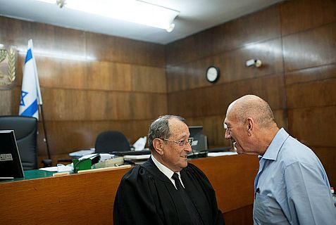 Former prime minister and Jerusalem mayor Ehud Olmert speaks with his attorney Eli Zohar in the courtroom of the District Court in Tel Aviv.