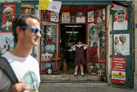 A tourist walks past a Christian souvenir shop with pictures of Pope Francis near Manger Square, on May 21, 2014.