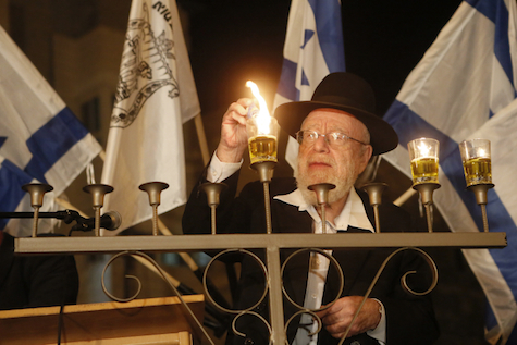 Rabbi Dov Lior lights Chanukah candles outside Beit haMachpela, in Hebron.