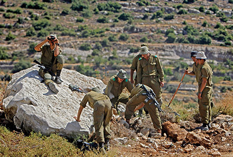 Israeli soldiers look under rocks near Hebron during the search for three kidnapped Israeli teens, missing since June 12.