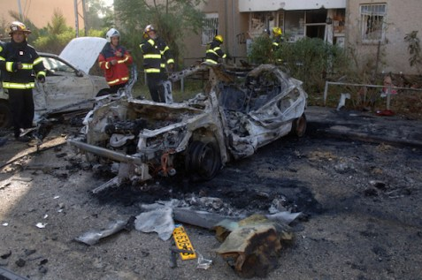 Israeli forces inspect a car after a Grad rocket attack in Beer Sheva, November 20, 2012.
