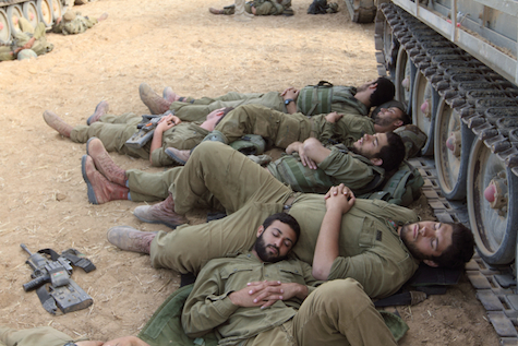 IDF soldiers rest while awaiting orders to enter Gaza.
