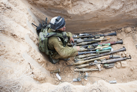 IDF soldier guards weapons caught inside a tunnel near Kibbutz Sufa, July 17, 2014,