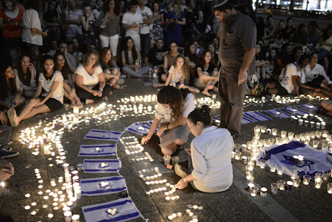 Israeli teenagers light candles in memory of Eyal Yifrah, Gil-Ad Sha'ar and Naftali Fraenkel, June 30, 2014