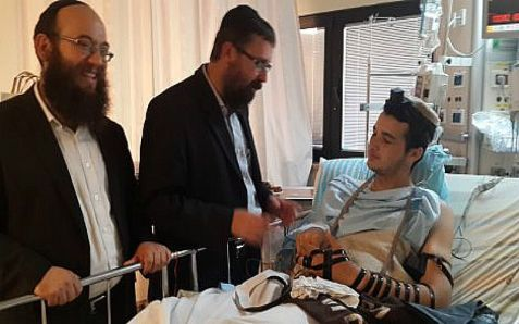 Wounded soldiers receives from Young Chabad new tefillin to replace his set that was destroyed in clashes with Hamas,