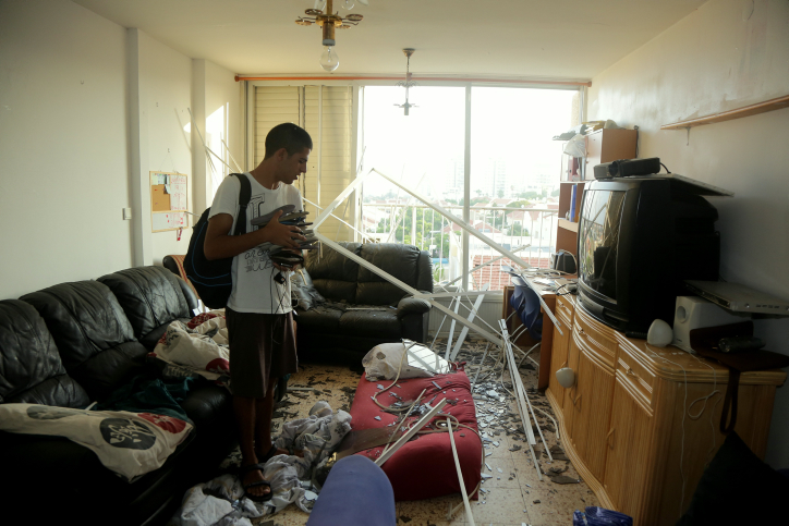 Ashkelon resident inspect house following missile strike, August 26, 2014.