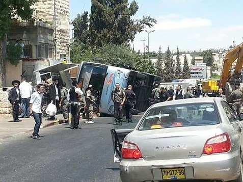 Bus flipped by tractor, in Jerusalem.