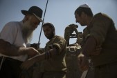 A Chabad man helps some IDF soldier put on T'fillin