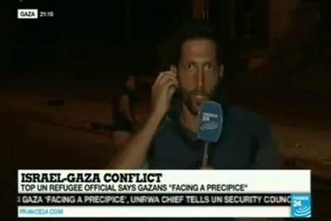 A reporter in Gaza, as a rocket is fired right behind him.