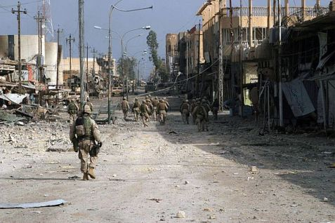 US Marines walk a city street in Fallujah, heavily damaged by the fighting. (2004)