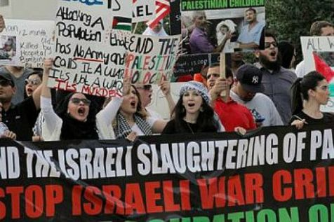 """Anti-Israeli protesters in Texas hold signs """"They're both the same,"""" written next to pictures of Hitler, an equals sign, and Netanyahu."""