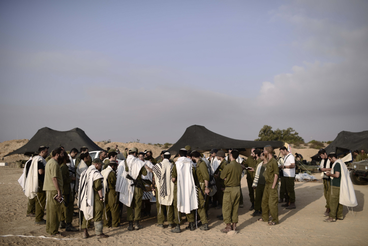 IDF reserve soldiers recite morning prayers near the Israel- Gaza border, August 5, 2014.