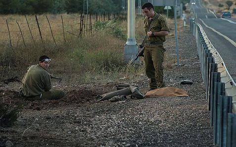 Israeli soldiers seen collecting the remains of a rocket fired from Syria into Israel, landing near Kibbutz El Rom in the Golan Heights in July.
