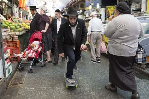 Skateboarding down the streets of Jerusalem's Mahane Yehuda open air market at holiday time.