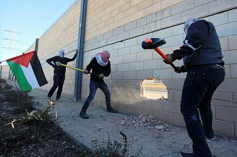 Arabs with sledgehammers break the security wall between Jerusalem and Ramallah.