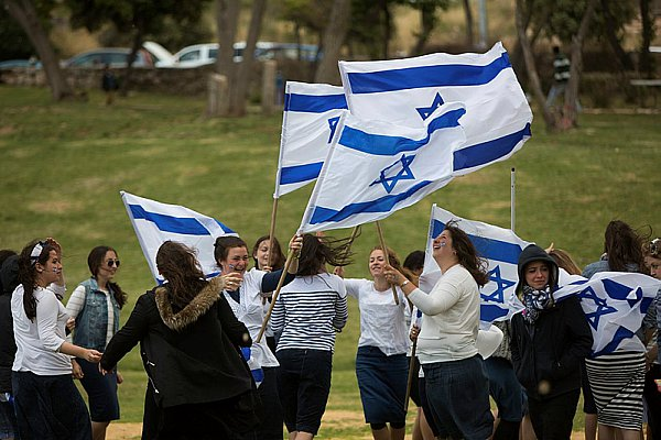 Girls dance with the national flag to celebrate Yom Ha'Atzmaut.