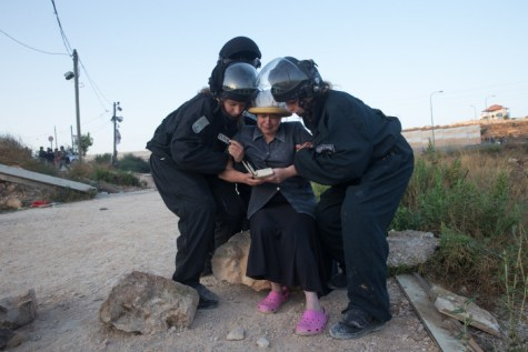 An Israeli woman weeps as she prays while police drag her away at Beit El protest.