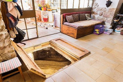 The concealed wooden doors opened to reveal stairs leading to an ancient mivkah.  The mikvah is a Jewish ritual pool that has been used for thousands of years -- to this day --  for various purification purposes.