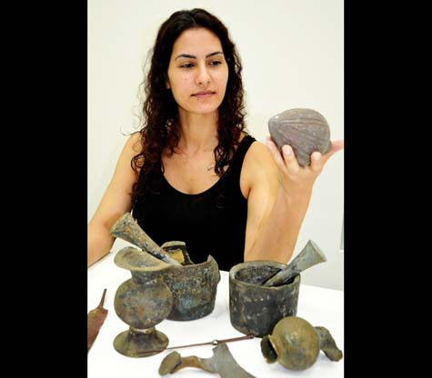 An Israel Antiquities Authority employee examining the finds. Photographic credit: Amir Gorzalczany, Israel Antiquities Authority.