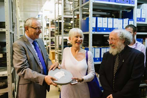 Dame Helen Mirren holds one of the 10,000 reels of film at the Hebrew University's Steven Spielberg Jewish Film Archive. Also pictured: Hebrew University President Prof. Menahem Ben-Sasson (L) and Dean of the Faculty of Humanities, Prof. Dror Wahrman. / Courtesy the Hebrew University of Jerusalem, photo by Dor Kedmi