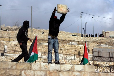 Arabs try to drop a stone block on Israeli soldiers in Ras al-Amud, Jerusalem.  (Archive: January 2009)
