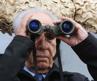 Israeli President Shimon Peres looks trhough binoculars durign a visit at the Northern Israeli border.