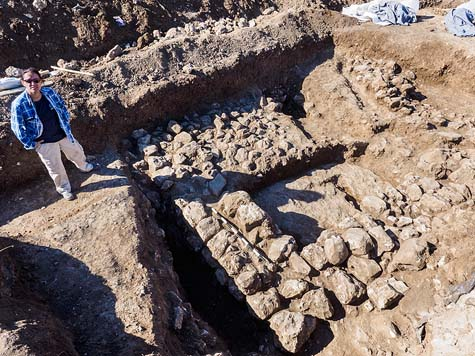 Excavation director Ronit Lupo of the Israel Antiquities Authority next to the remains of the ancient house.