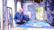 Roberto Burle Marx painting a tablecloth in the loggia of his home, 1980s; the azulejo tile walls and chandelier composed of fruit and flowers on a metal armature are his work. / The Jewish Museum