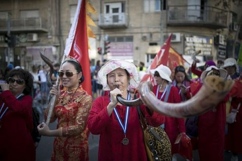 Southeast Asians blow the shofar as they march through the streets of Jerusalem in the annual parade on the Jewish Festival of Sukkot, the Feast of Tabernacles.