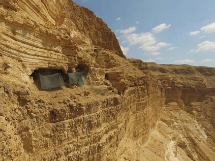 The cave where the archaeological excavation is being conducted is situated c. 80 meters from the top of the cliff and c. 250 meters above the base of the canyon. Photographic credit: Guy Fitoussi, courtesy of the IAA Unit for the Prevention of Antiquities Robbery.