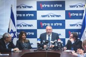 "Yisrael Beyteinu leader Avigdor Liberman speaking to the press against a background wallpapered with the slogan: ""A word is a word!"""