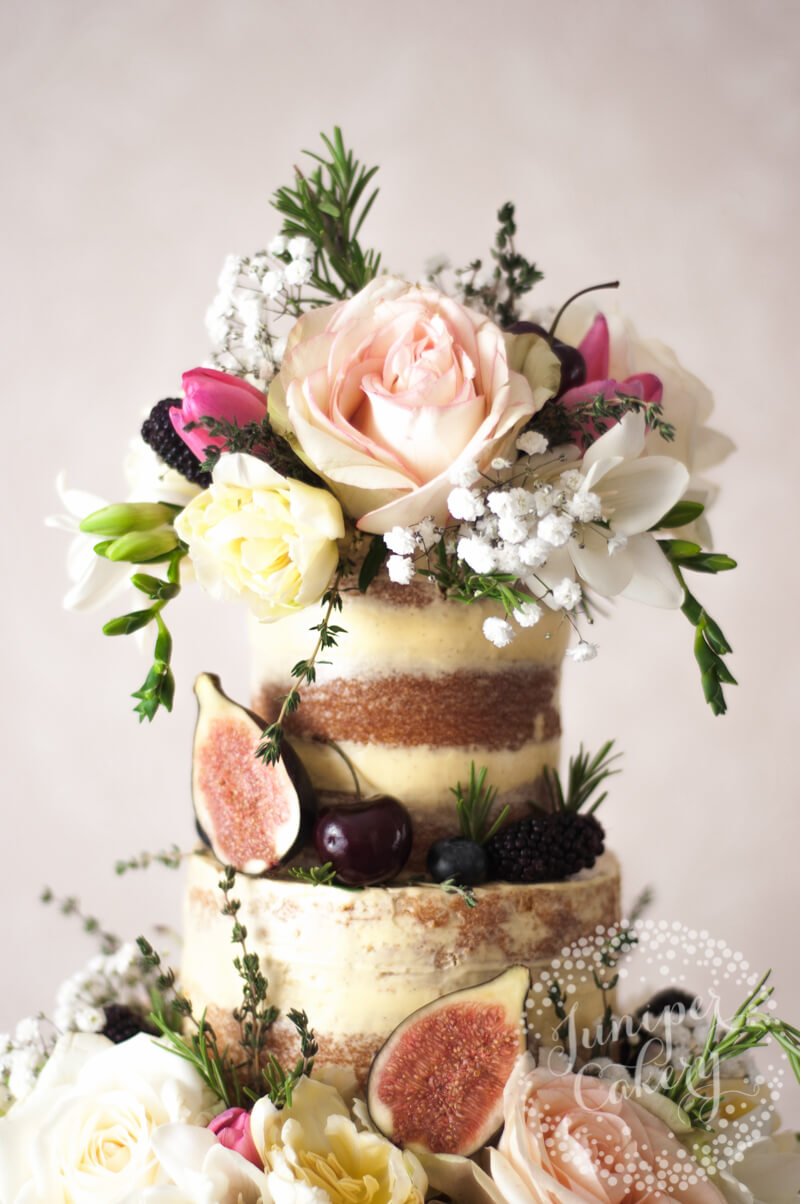 Stunning semi-naked wedding cake with florals and fruits by Juniper Cakery