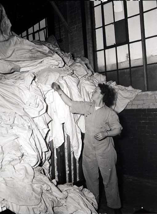 Private N. McCosh sorting a pile of laundry at Camp Borden, Ontario, March 16th, 1945.