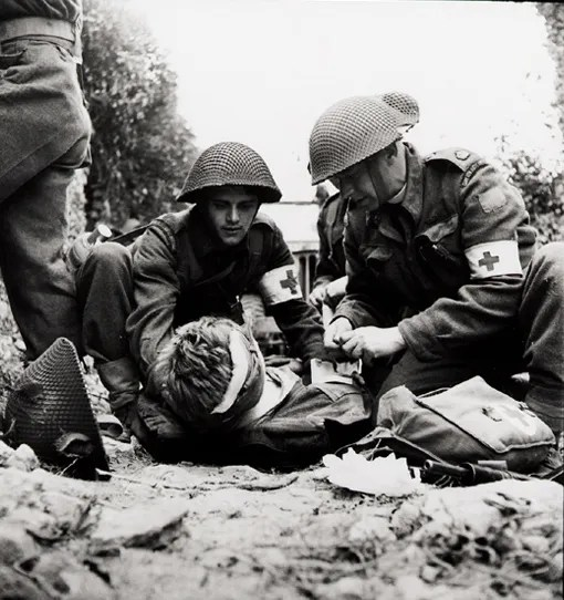 A wounded man of the 3rd Canadian Infantry Division receives first aid from members of the Regimental Aid Post, with help from the regiment's Padre, near Caen, Normandy, 15 July 1944.
